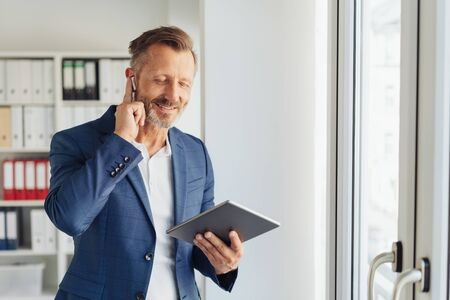 Middle-aged businessman absorbed in his music as he listens to tunes on his tablet on an earbud with closed eyes and happy smile