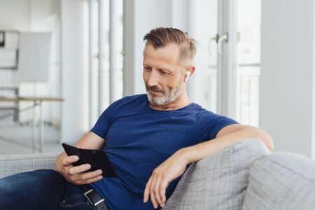 Relaxed casual man reading a text message or news on his mobile phone with a serious expression as he relaxes on a sofa