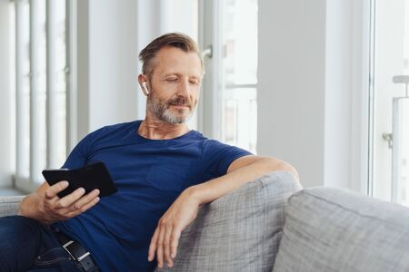 Middle-aged man relaxing at home with his music listening to tunes on his mobile phone using an ear bud with closed eyes