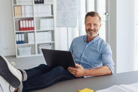 Lächelnder moderner selbstbewusster lässiger Geschäftsmann, der mit seinen Füßen auf dem Schreibtisch mit einem Laptop arbeitet Standard-Bild
