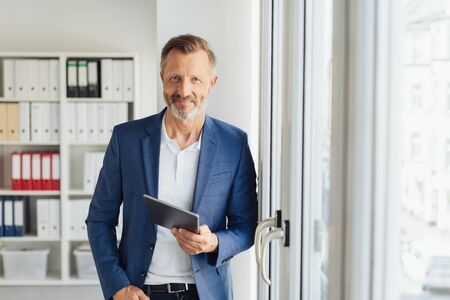 Smart relaxed confident senior businessman holding a tablet standing leaning against a glass door at the office smiling at camera