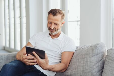 Man relaxing at home on a comfortable sofa with his tablet pc reading online with a quiet smile of pleasure