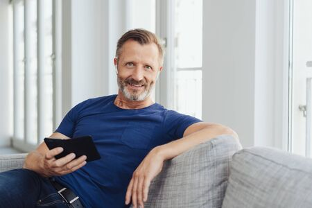 Relaxed attractive middle-aged man on a sofa sitting listening to music on his mobile phone using an earbud as he smiles at the camera