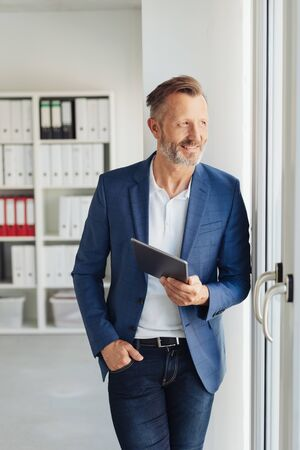 Smart businessman standing waiting with a tablet-pc in his hand staring through a glass door at the office with a preoccupied smile