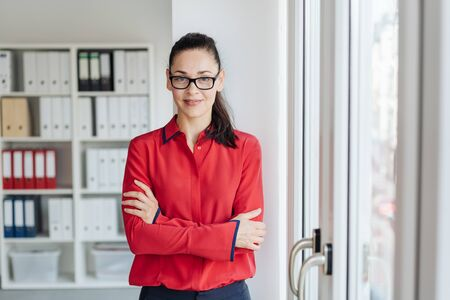 Self-assured young businesswoman wearing glasses standing with folded arms in the office looking at camera with a quiet smile