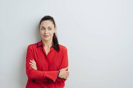 Atractiva mujer joven con cola de caballo y brazos cruzados con una colorida blusa roja mirando a un lado con una expresión seria pensativa contra una pared blanca con espacio de copia
