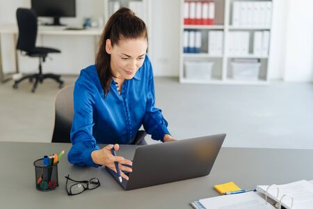 Young businesswoman immersed in her work sitting at her desk reading on a laptop with a look of concentration