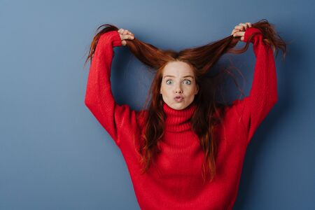 Temperamental young woman pulling her long red hair and glaring at the camera in frustration and anger over a blue studio background with copy space