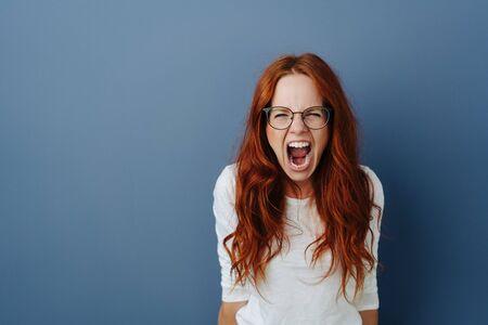 Giovane donna arrabbiata che fa i capricci urlando alla telecamera con un'espressione furiosa su uno sfondo blu per studio con spazio di copia