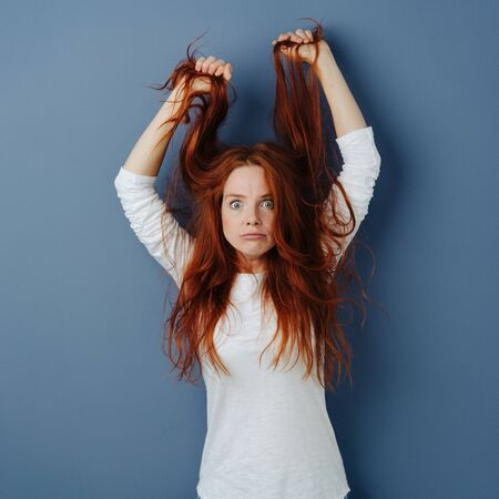 Angry young woman pulling her long red hair as she glares balefully at the camera in a rage over a blue studio background with copy space