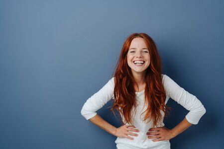Young woman having a good giggle standing with hands on her waist laughing at the camera over a blue studio background with copy space