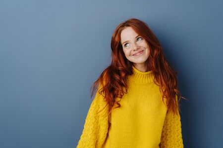 Simpering young woman with a coy smile looking aside with a smile as she flirts over a blue studio background with copy space Banco de Imagens