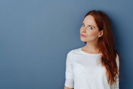 Jeune femme sceptique astucieuse regardant la caméra avec une expression aux yeux grands ouverts sur un fond de studio bleu avec espace de copie