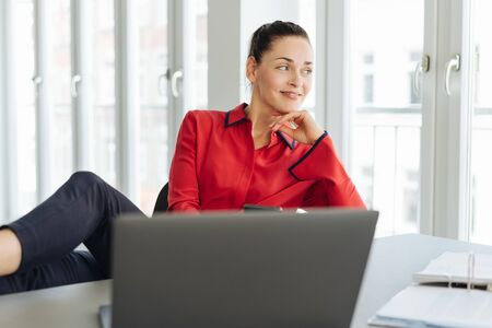 Relaxed businesswoman taking a break sitting back with her feet up on the desk looking out of a window with a happy smile