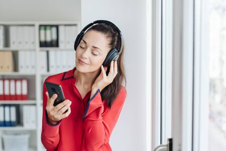 Blissful young woman listening to music on headphones as she enjoys her break in the office standing with closed eyes and a smile of contented pleasure