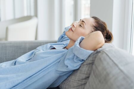 Exhausted young woman relaxing on a sofa lying back with her hands behind her head and closed eyes with a quiet smile of pleasure