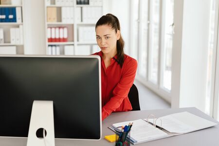 Serious sceptical young businesswoman sitting working at a computer looking at the camera with a thoughtful expression Stock Photo
