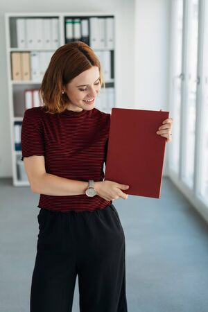 Stylish young job applicant display her CV in a red binder in an office with a happy smile