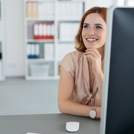 Happy young businesswoman sitting reminiscing looking up with a happy smile and faraway expression at a desk in the office