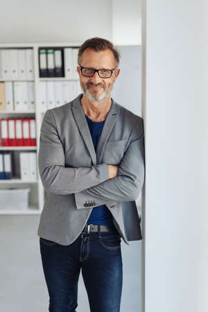 Relaxed stylish businessman smiling at camera as he stands with folded arms leaning against a wall in the office