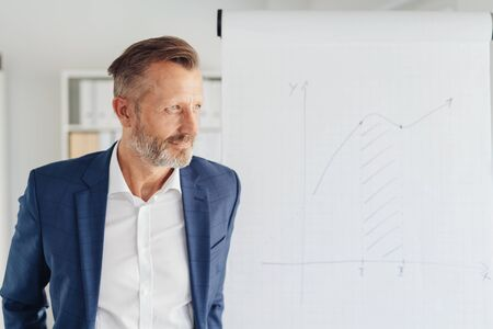 Stylish businessman staring thoughtfully aside as he stands thinking in a bright airy office with copy space