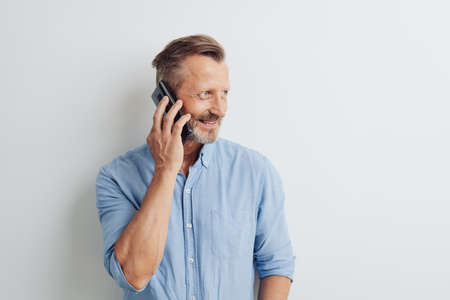 Casual man standing chatting on his mobile phone looking aside with a smile over a white studio background with copy space
