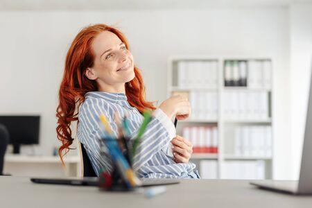 Jeune femme d'affaires assise à rêvasser avec un sourire béat sur son visage alors qu'elle se détend pendant une pause au bureau Banque d'images