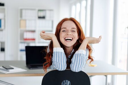 Laughing young redhead woman leaning over the back of a chair at the office grinning happily at the camera