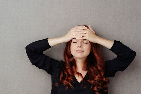 Woman taking a moment to relax and catch her thoughts standing with her hands clasped on her forehead, eyes shut and a serene expression over grey Banco de Imagens