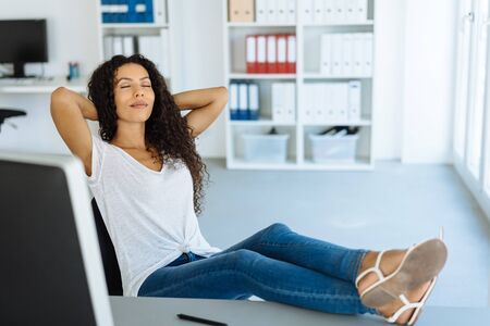 Young woman taking a break at the office sitting back with her feet on the desk and eyes closed relaxing Banco de Imagens