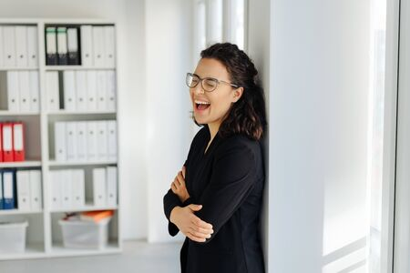 Young businesswoman enjoying a good laugh by herself as she stands relaxing against an interior wall in the office with copy space