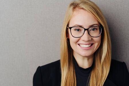 Fijne jonge blonde vrouw met een bril die naar de camera kijkt met een brede grijns over een grijze studioachtergrond met kopieerruimte