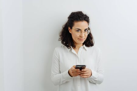 Cute young woman glancing up at the camera as she stands texting a message on her mobile against a white interior wall with copy space