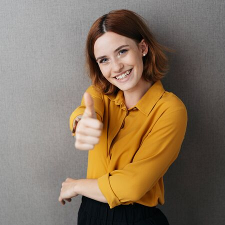 Excited elated woman giving a thumbs up gesture with a beaming happy smile over a grey background in square format