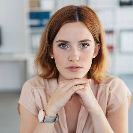 Serious young woman with a deadpan expression resting her chin on her hands as she stares intently at the camera Stock Photo