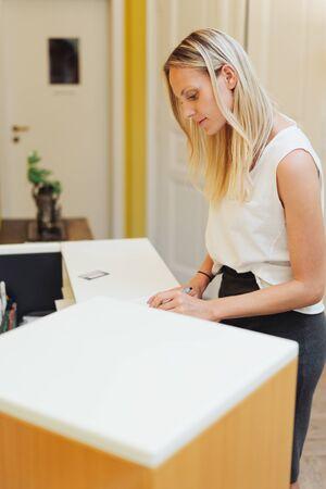Patient complétant ses coordonnées à une réception de chirurgie debout au comptoir remplissant un formulaire