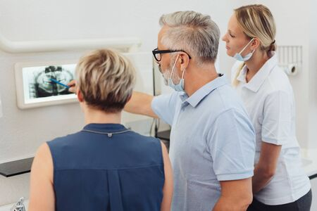 Dentists explaining an x-ray to a female patient showing her on a monitor watched by his dental nurse