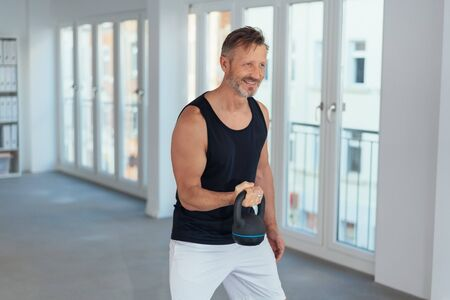 Happy motivated man lifting a kettlebell weight during a workout in a corporate gym at the office Foto de archivo