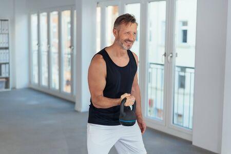 Heureux homme motivé soulevant un poids kettlebell lors d'une séance d'entraînement dans une salle de sport d'entreprise au bureau Banque d'images