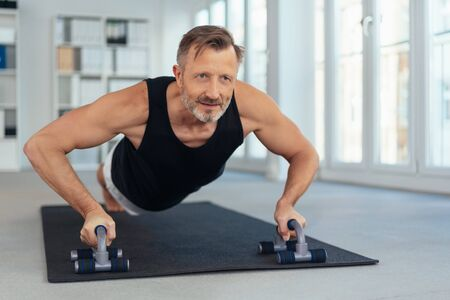 Sportive middle-aged man doing push-ups on handles on black mat in office, viewed from his front Standard-Bild - 139484718