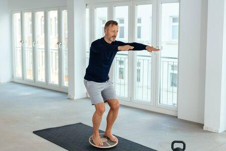 Hombre haciendo ejercicios de equilibrio y control muscular en un amplio y luminoso gimnasio urbano en un concepto de salud y fitness