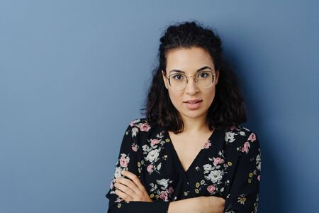 Front portrait of pretty and young brunette woman in glasses with curly hair, standing with her arms folded and with questioning look towards camera, against plain blue wall with copy space