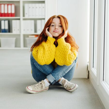 Bored young woman in her twenties sitting cross legged on the floor in the office in jeans and sweater looking glumly at the camera