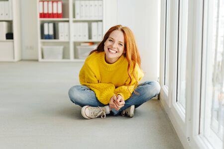 Young woman sitting on the floor in the office in jeans and sneakers looking at the camera with a happy beaming smile