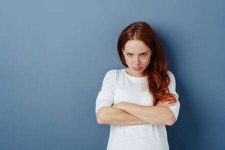 Sulky young redhead woman standing with folded arms and head lowered pouting at the camera on a blue studio background with copy space