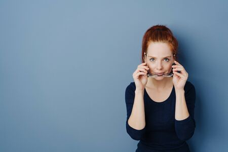 Pretty young redhead woman holding her spectacles below her chin as she peers over the top at the camera on a blue studio background with copy space