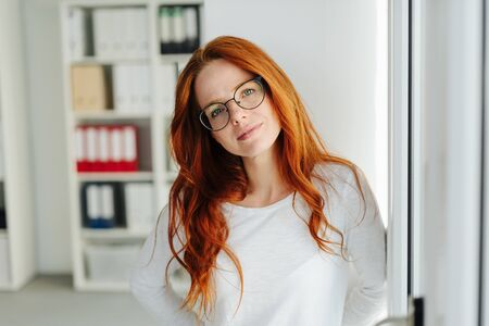 Sincere serious young redhead woman looking quietly at the camera with a thoughtful expression inside an office