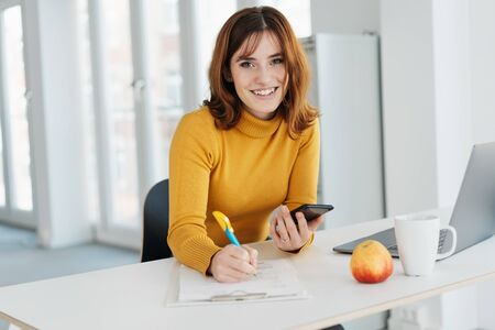 Sincere young businesswoman looking quietly at camera with a smile as she sits working at a desk in a high key modern office