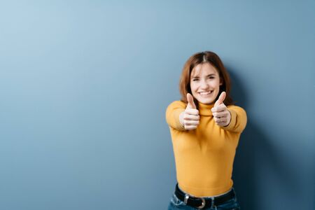 Elated young woman giving a double thumbs up of success with a beaming happy smile against a blue studio background with copy space Stockfoto