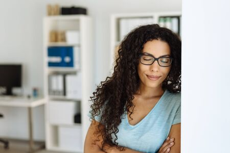 Attractive African businesswoman wearing glasses taking a moment to relax leaning against an office wall with folded arms Banco de Imagens